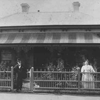 Image: a man and a woman stand behind a wooden fence in front of a bluestone cottage with tin roof and verandah. The man stands at the gate and wears a dark suit and bowler hat, the woman who is to the right of the photograph wears a white dress.