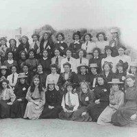 Image: a large group of girls in early 20th century dresses, some wearing straw hats, pose in four rows for this formal school photograph.