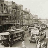 Image: a city street busy with pedestrians, electric trams and buses. In the left foreground is the Adelaide-Glenelg Railways Bus, a double decker with an open top, its passengers enjoying the sunshine. One of the buildings is in process of remodelling.