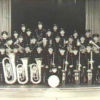 Image: A large, all-male brass band poses with their instruments on a stage