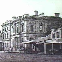 Image: a large two storey stone public building with arched windows on the ground floor and rectangular windows with triangular pediments above. The entrance to the building is recessed and flanked by columns