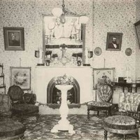 Image: Black and white photograph of interior of room, with floral-print furniture and wallpaper