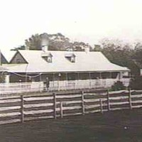 Image: Black and white photograph of homestead with outbuildings and a wooden fence in foreground