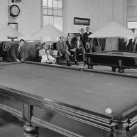 Image: a group of men sit or stand around two large billiard tables.