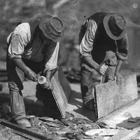 Image: Two men in hats are bent over splitting slate