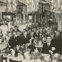 Image: a large group of men in dark suits are seated around long tables dressed with white tablecloths and large floral arrangements. Women in white dresses and hats stand in lines on either side of the room and streamers hang from the roof.