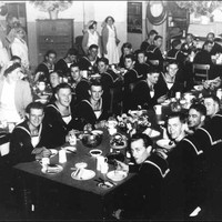 Image: A group of men in sailors uniforms sit around tables while women in white uniforms serve them food
