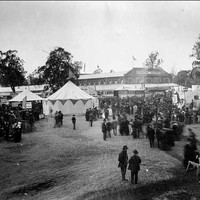 Image: a crowd of men and women in 1870s clothing stand amongst tents and agricultural displays. In the background a large building can be seen.