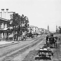 Image: Horses and buggies travel down a wide dirt road. In the distance two towers (the Town Hall and Post Office) can be seen on either side of the street.