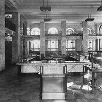 Image: the interior of a bank which is lined with marble and features a mezzanine balcony level, double height arched windows and square columns
