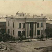 Image: a two storey stone building with a rectangular floorplan and an entrance flanked by huge, two storey columns stands on a street corner and surrounded by other commercial and public building