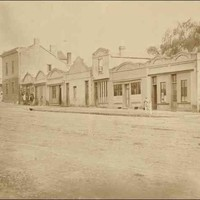 Image: a row of single and double storey terraced buildings with a variety of rooflines, including arched parapets and exposed gable ends, fronting a dirt road.