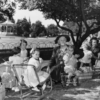 Image: Three women and seven children in 1950s clothing sit on low chairs in a park enjoying a picnic. In the background a rotunda can be seen.