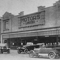 "Image: a group of men in early 20th century clothing pose around a number of cars parked outside a two storey building with a sign reading ""Motors Limited"""