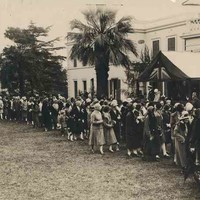 Image: A line of people in 1920s clothing stand next to the front of a white, two-storey building