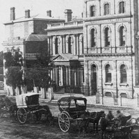 Image: horse drawn carriages are stopped on a dirt road outside of two public buildings. The one on the right is three stories while the one in the centre of the picture is two stories and features a columned portico with a decorative triangular pediment.
