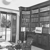 Image: A room containing shelves full of books and a wooden desk with chair