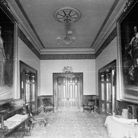 Image: An interior hallway with large painted portraits hanging from each wall and a double door at the end