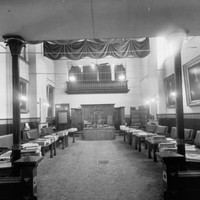 Image: leather bench seats sit behind desks facing inwards and arranged along the walls of a large room which is decorated with large portraits. At the far end of the room is a more ornate desk with three individual seats.