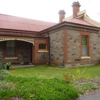 Image: A single storey bluestone building with red brick quoins, red tin roof with cream details and a number of brick chimneys. The building also has a verandah and decorative stained glass on two of its windows.