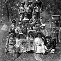 Image: A group of boys and girls, some holding sticks and flowers, with two young men