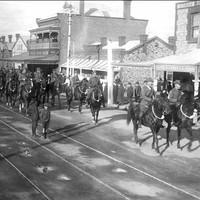 Image: a troop of mounted soldiers ride along a city street while women on the store balconies and two boys standing on the tram line watch on.