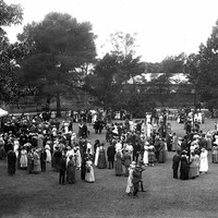 Image: a large group of people in 1920s fomalwear mingle on a lawn in front of a large building. A tent with white roof is visible at image left