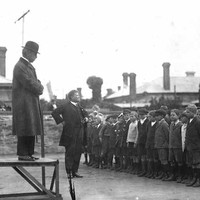 Image: a man in a coat and bowler hat stands on a small platform while below a headmaster in a dark suit addresses a group of boys and girls standing in neat rows.
