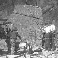 Image: Four men stand around a large piece of slate which is suspended by chains in a quarry