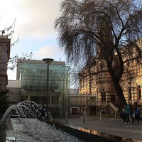 Image: A modern, glass-fronted building connects two multi-storey historic buildings. A modern fountain sculpture is in the foreground