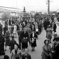 Image: Crowd of people walking passed buildings