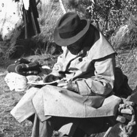 Image: A man in a trenchcoat and fedora sits in a chair and writes on a pad of paper in a scrubby clearing. Another man uses a shovel to dig a hole nearby