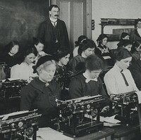 Image: A group of Caucasian men and women dressed in early twentieth century attire practice typing in a classroom. A moustachioed male Caucasian instructor looks on in the background