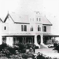 Image: A large, two-storey mansion stands at the top of a hill surrounded by trees and vegetation. A small group of men and women stand in front of the house