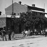 Image: dozens of men in early 20th century working clothes stand along a dirt road lined with single and two storey buildings and mature trees laying a telegraph cable.