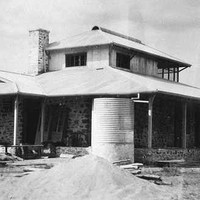 Image: A single-storey stone building with gabled roof and wraparound verandah. A corrugated metal water tank and evidence of construction is visible in the foreground