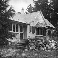 Image: A single-storey cottage nestled amongst several large cedar trees. The front of the house is bordered by a low stone wall
