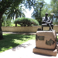 Image: bronze statue of seated woman with books