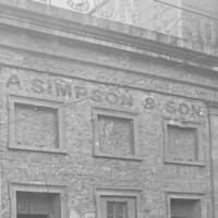 Image: A two-storey bluestone building, the windows in the upper floor of which have been blocked up with stone and/or brick. A sign above the building reads A. Simpson & Son