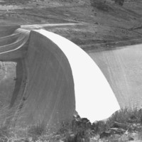 Image: A large concrete dam located among rolling hills. To the right of the dam is a reservoir of water, and to its left a dry rocky chasm