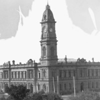 Image: A large, two-storey stone building with a tall clock tower protruding from one corner. A tree-lined park is visible in the foreground