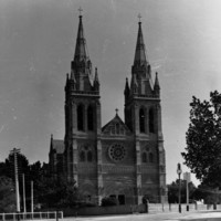 Image: A large, Gothic stone cathedral with two tall spires and a central window with floral motif