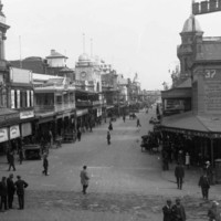 Image: A view from a busy intersection with many people in 1920s attire walking or cycling, and a mix of horse drawn and motor vehicles. The view is centred on a street lined with 2 and 3 storey commercial buildings, most with verandahs and/or balconies.