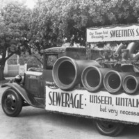 Image: truck carrying large pipes and sewer signage