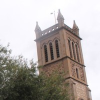 Image: A sign for Holy Trinity Church stands in front of the large stone church tower
