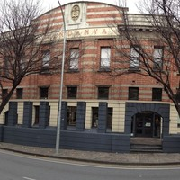 Image: panorama shot of a red brick building of three storeys, taken in winter with barren trees outside