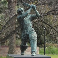 Image: A bronze statue of a cricket batsman standing in a 'driving' pose