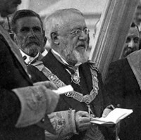 Image: A bearded middle-aged Caucasian man in Masonic ceremonial vestments officiates at a ceremony to lay a building's foundation stone