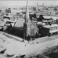 Image: aerial view of stone church with large steeple on street corner