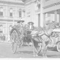 Image: Two women and a child inside a decorated horse-pulled cart